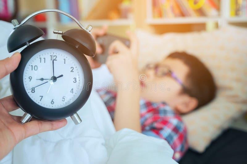 Entregue a mostra para fora para o despertador na manhã, menino que joga no gam imagem de stock