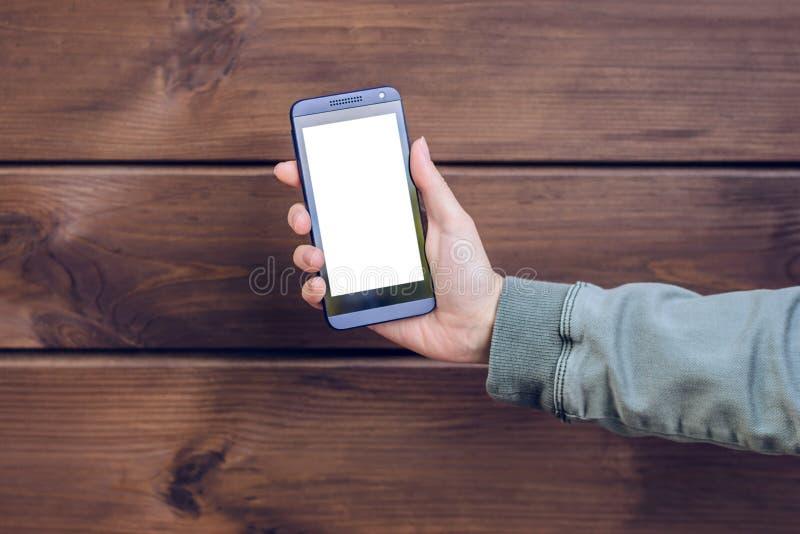 Entregue mostrar o telefone celular com espaço emtpy contra técnico moderno do smartphone esperto móvel de madeira marrom do tele foto de stock royalty free