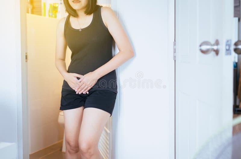 Entregue a mulher asiática que guarda seu gancho, necessidade fêmea de fazer xixi um toalete imagem de stock royalty free