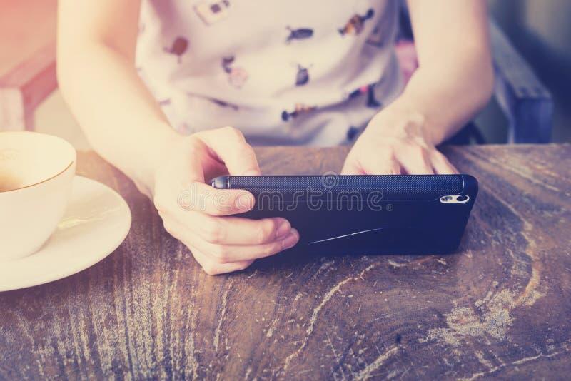 Entregue a mulher que usa o smartphone na cafetaria e na luz suave fotografia de stock