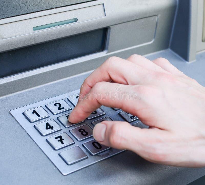 Entregue números de PIN entrando na máquina do banco do ATM imagem de stock