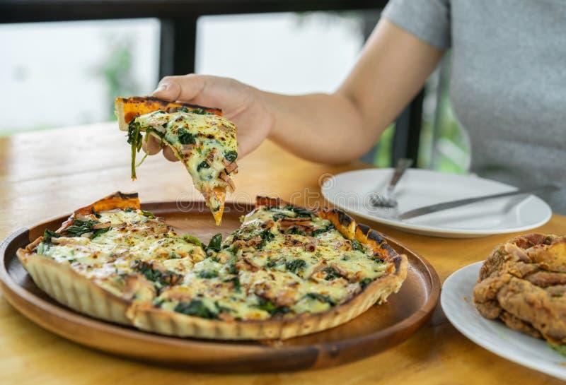 Entregue o agarramento de uma parte de pizza de queijo dos espinafres e da cabra em um de madeira fotografia de stock royalty free