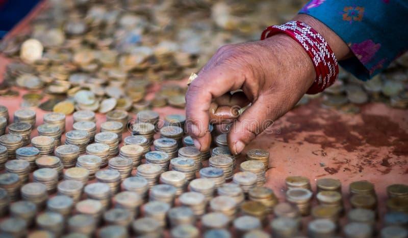 Entregue o arranjo de moedas na coluna de empilhamento, Nepal foto de stock royalty free