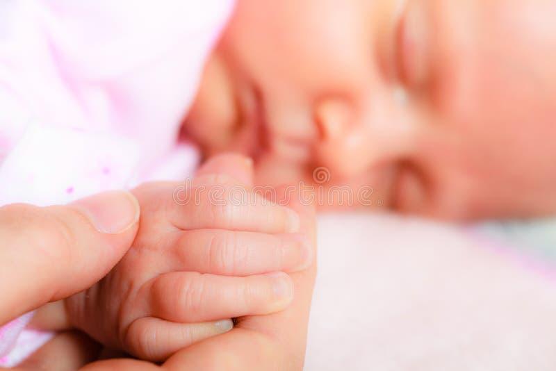 Entregue o bebê de sono na palma da mãe imagens de stock