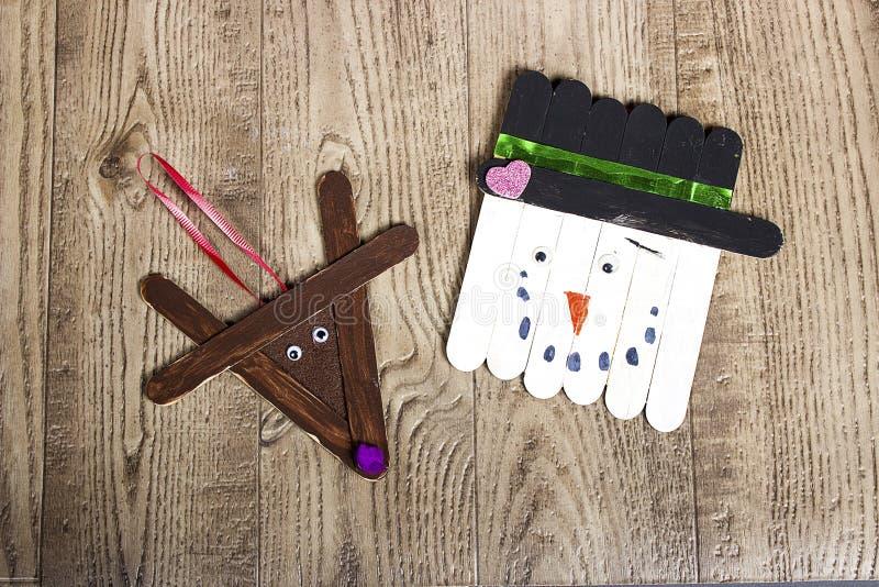 Entregue o boneco de neve crafted e a rena do picolé que colocam em um fundo de madeira da grão imagens de stock royalty free