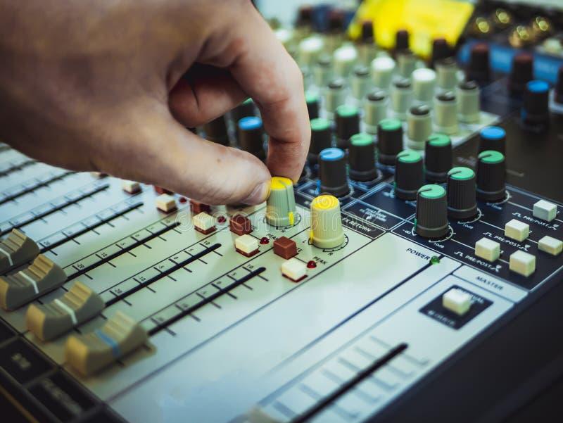 Entregue o botão de giro no equipamento do estúdio do controlador do DJ fotografia de stock