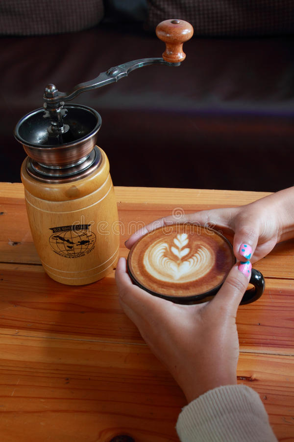 Entregue o café do marrom do vintage da posse e o moedor de café no ouro de madeira imagens de stock