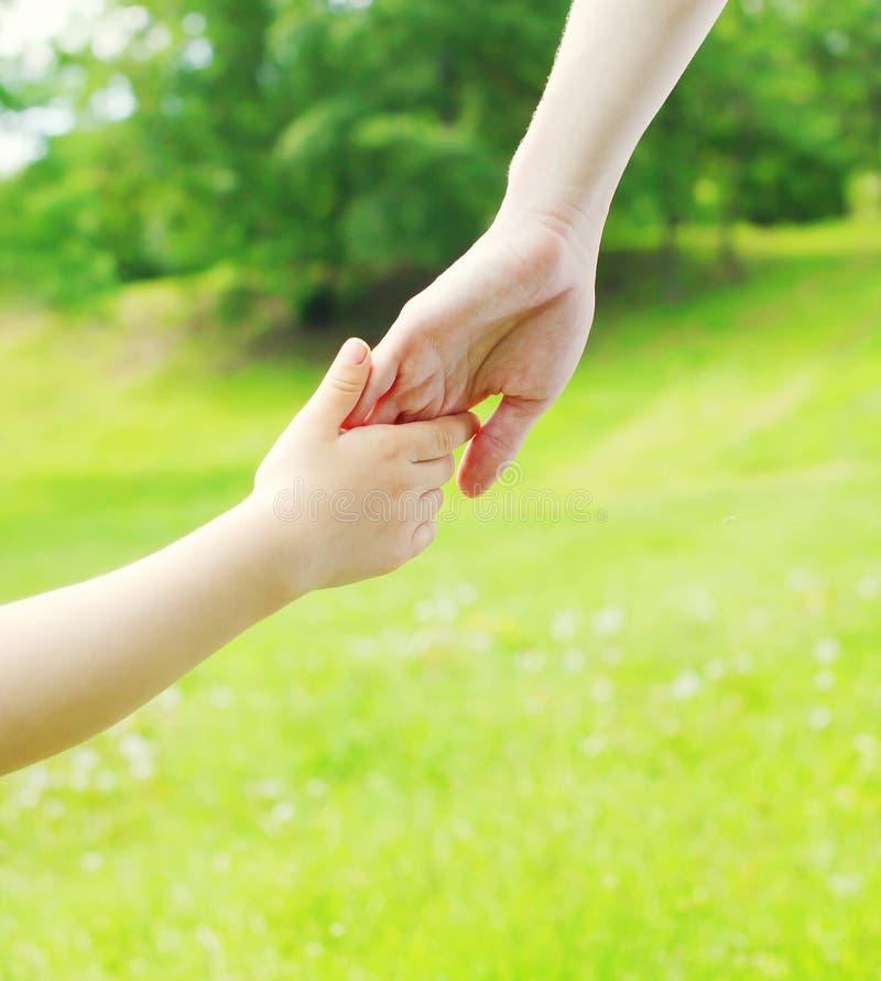 Entregue o close up da mãe da criança e da mão sobre o verão fotografia de stock