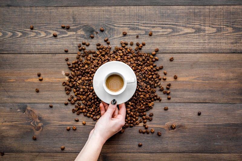 Entregue o copo da posse do café leitoso na opinião de tampo da mesa de madeira escura Fundo do café fotografia de stock