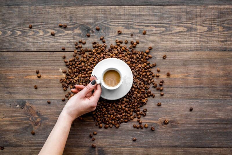 Entregue o copo da posse do café leitoso na opinião de tampo da mesa de madeira escura Fundo do café imagem de stock