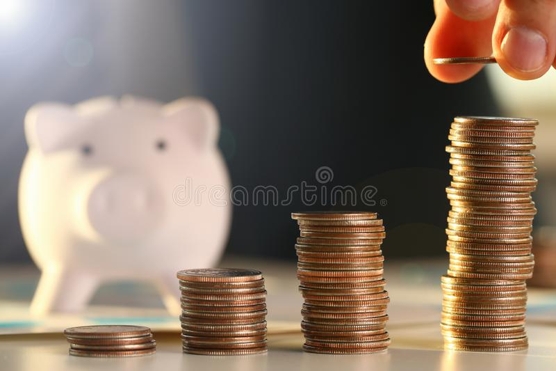 Entregue o homem de neg?cios que p?e o dinheiro de pino no porco fotos de stock royalty free