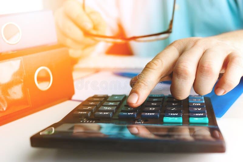 Entregue o homem que faz finanças e calcule-o na mesa sobre o escritório do custo em casa toned imagens de stock