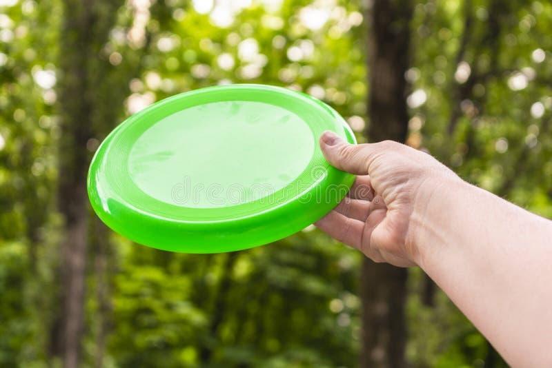 Entregue o jogo de um disco do frisbee no parque em um dia de verão fotografia de stock royalty free