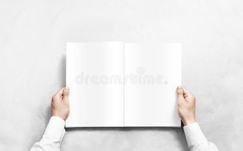 Entregue o jornal branco de abertura com o modelo das páginas vazias foto de stock royalty free