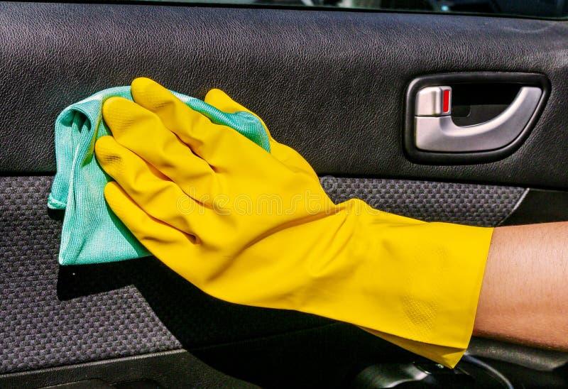 Entregue o painel interior de limpeza da porta de carro com o pano do microfiber Trabalhador na lavagem de carros imagens de stock