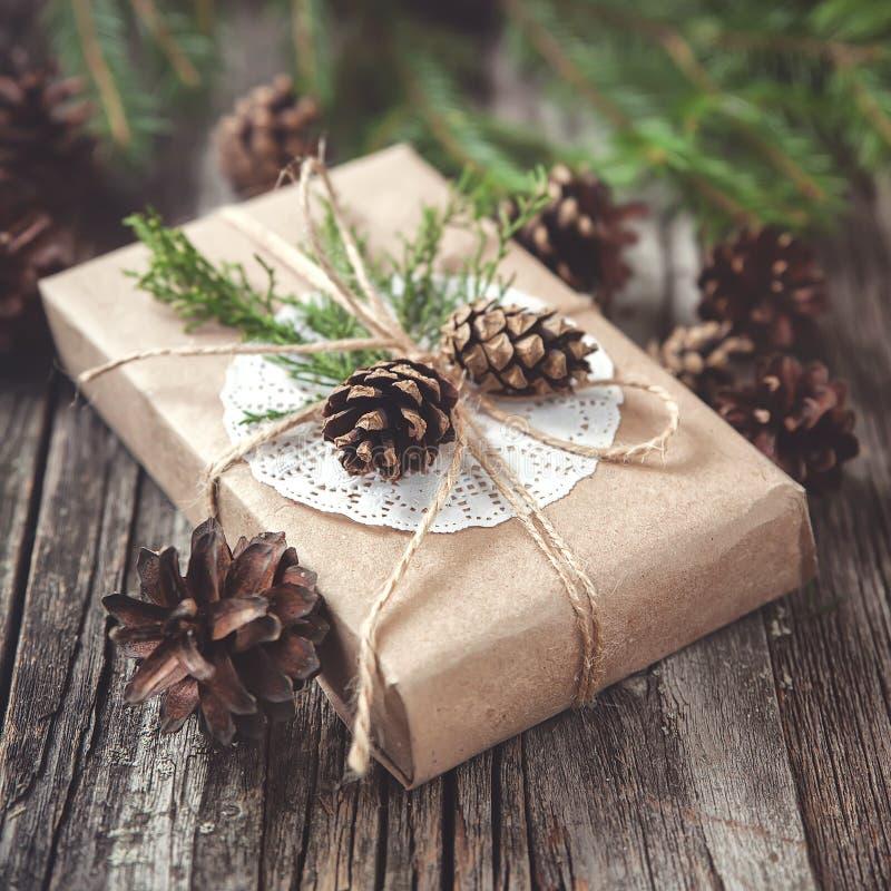 Entregue o presente crafted no fundo de madeira rústico com fotos de stock