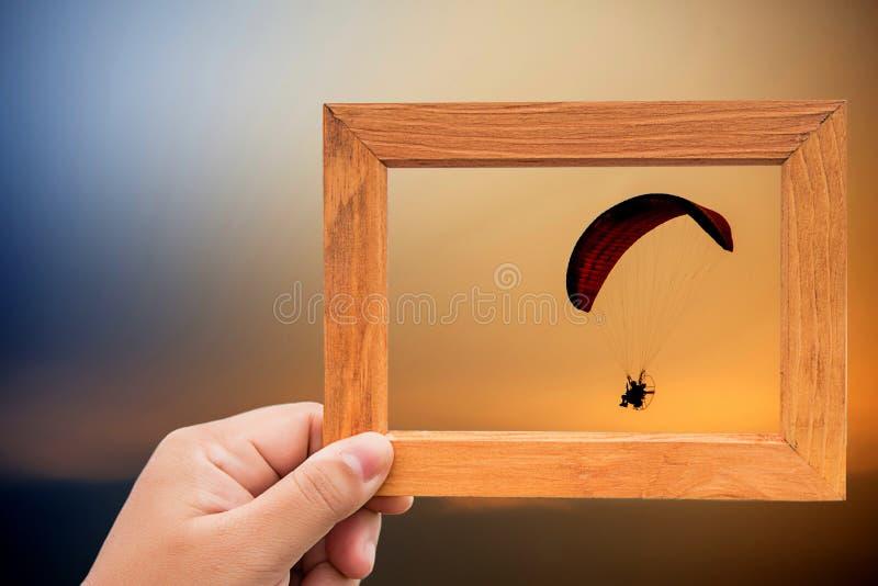 entregue o quadro da foto da posse e centre-se com o nascer do sol sobre o fundo mantenha a memória maravilhosa imagem de stock