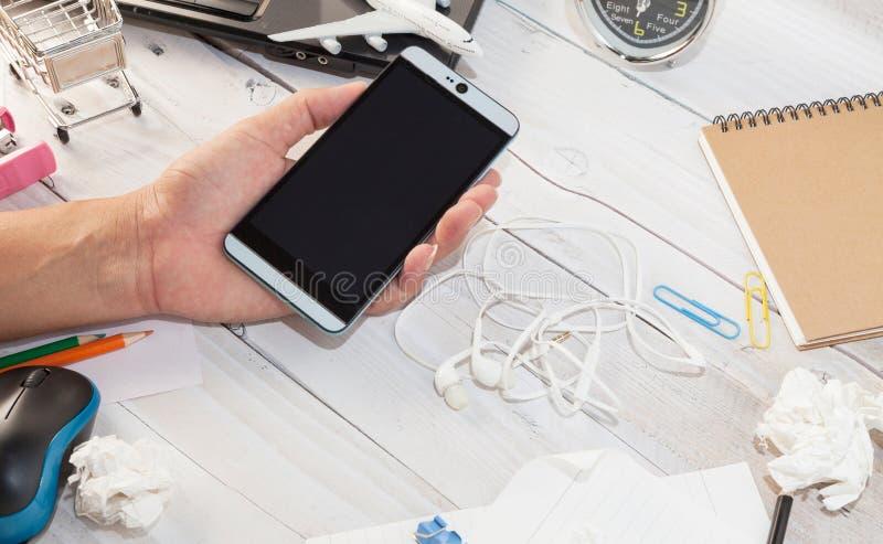 Entregue o smartphone guardando masculino na tabela de madeira branca do escritório com b fotos de stock royalty free