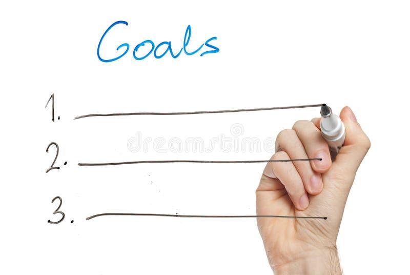 Entregue objetivos da escrita no whiteboard fotos de stock