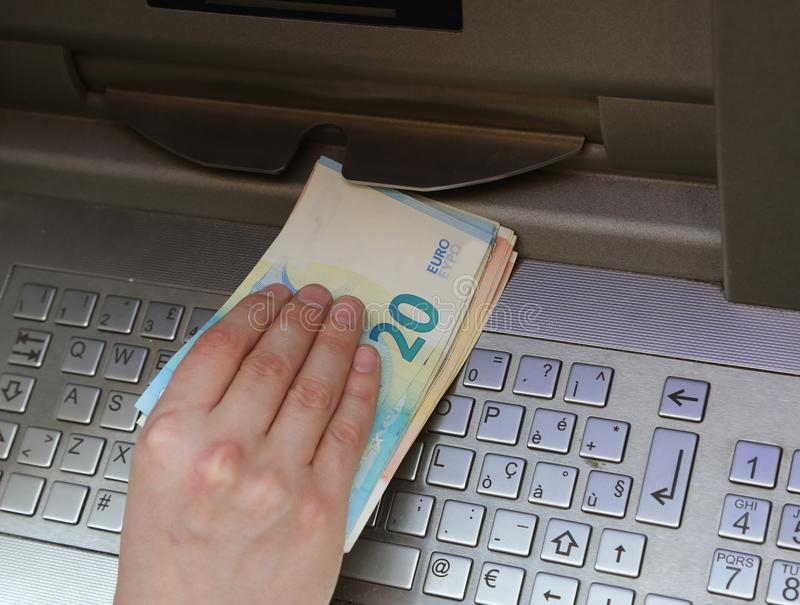 Entregue pegarar muito dinheiro de um ATM com euro- moeda foto de stock royalty free