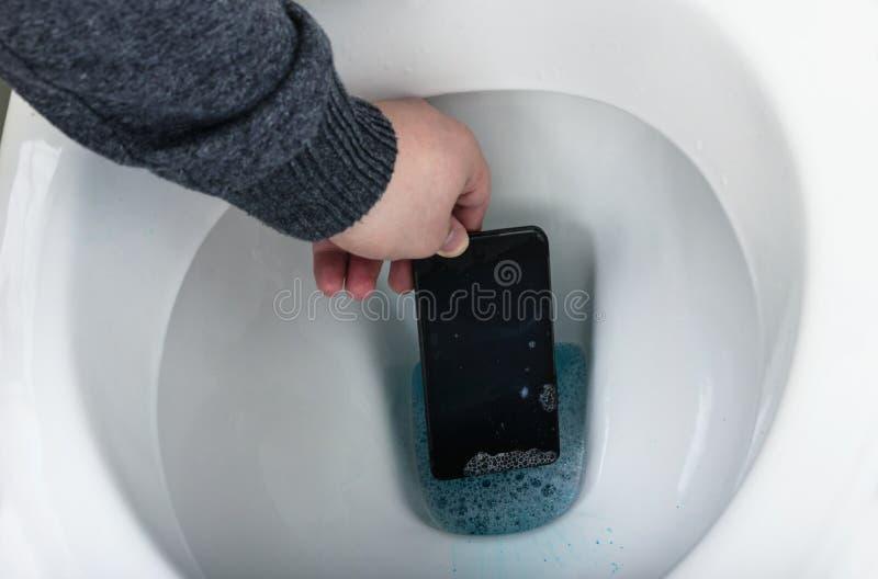 Entregue a pesca para fora do smartphone da água de toalete imagem de stock royalty free