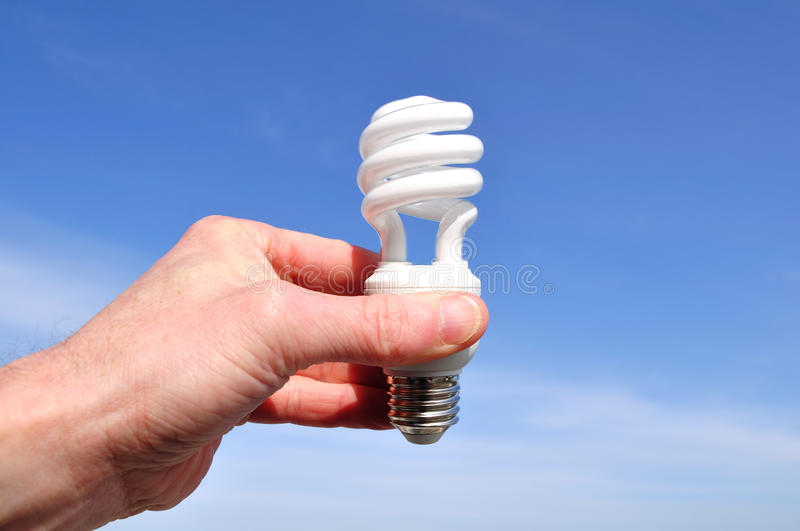 Entregue prender uma luz fluorescente compacta (CFL) foto de stock