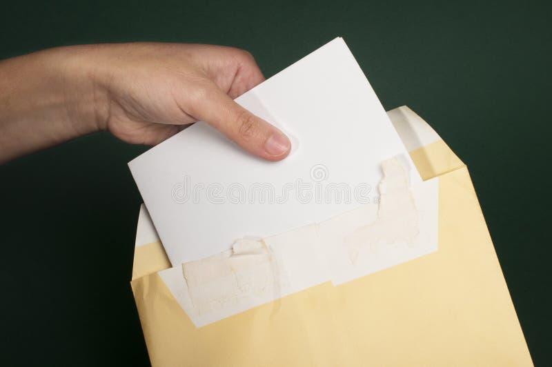 Entregue que abre uma letra do envelope marrom fotografia de stock