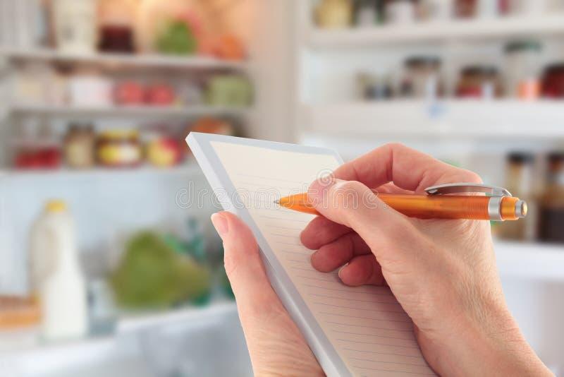 Entregue redigir uma lista na frente de um refrigerador aberto imagens de stock