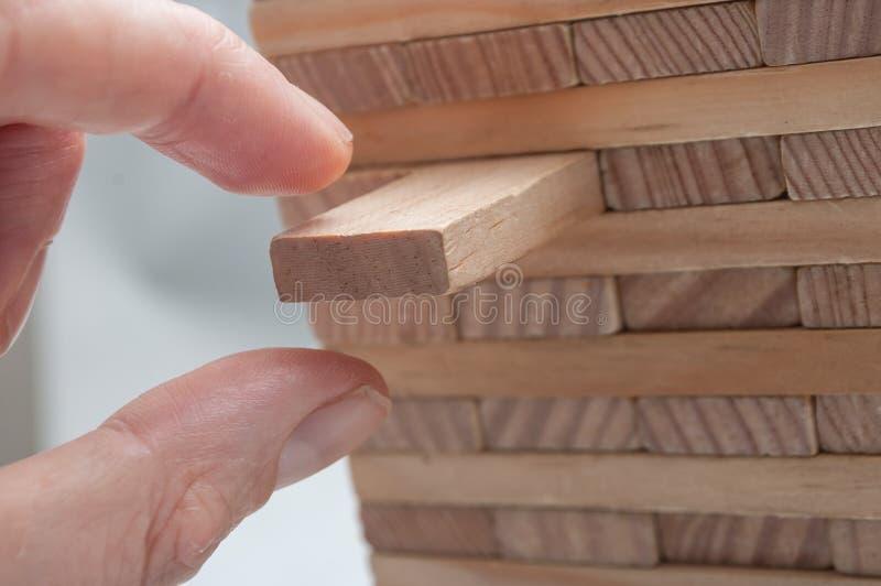 Entregue a tentativa para decolar a parte de tijolo de madeira do jogo da construção fotografia de stock royalty free