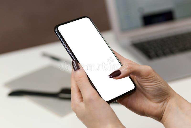 Entregue a terra arrendada o telefone esperto móvel com tela em branco fotografia de stock