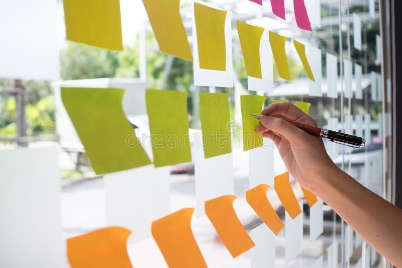 Entregue usando o post-it nota pegajosa com sessão de reflexão no papel de nota fotos de stock