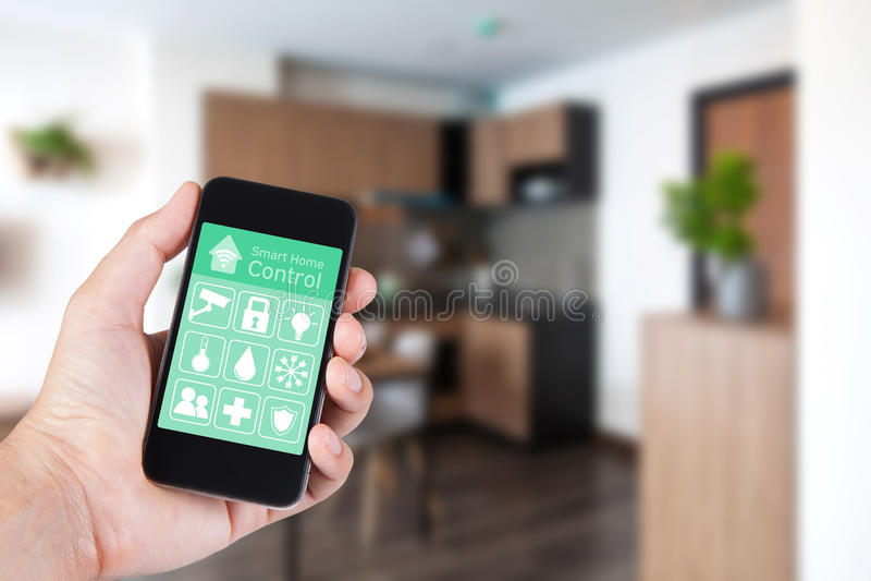 Entregue usando o smartphone à casa esperta app no móbil foto de stock