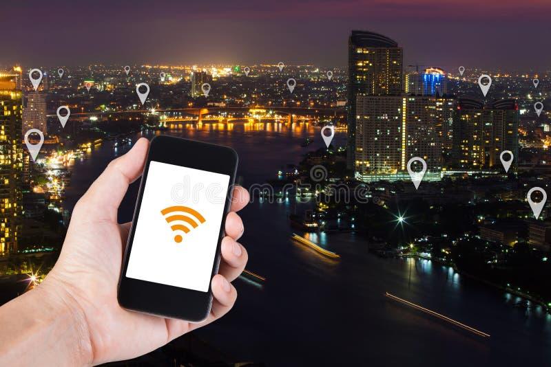 Entregue usando o smartphone que procura o lugar no pino do mapa na parte superior v foto de stock royalty free
