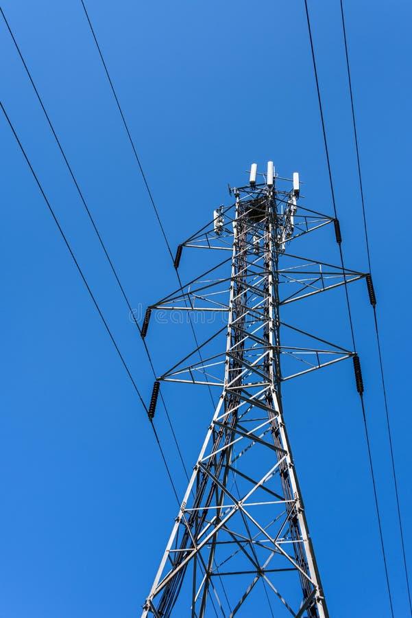 Entrelace a autossuficiente torre de serviço público de aço com linhas elétricas e antenas do painel para uma rede de comunicaçõe imagem de stock