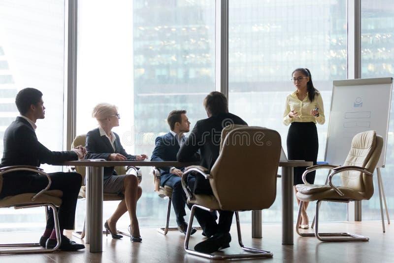 Entrenador asiático que da la presentación del negocio en la reunión multi-étnica del equipo del tablero imagen de archivo