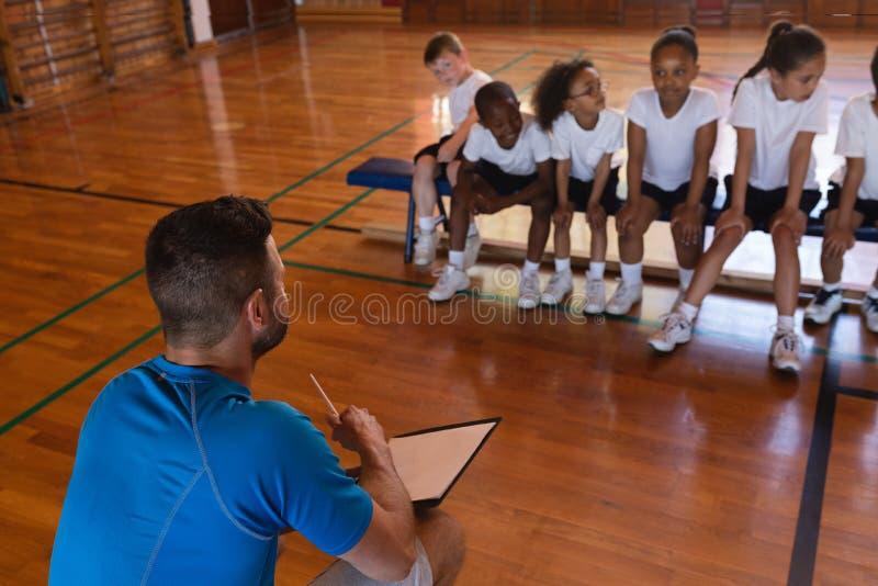 Entrenador de béisbol que habla con alumnos en la cancha de básquet fotos de archivo