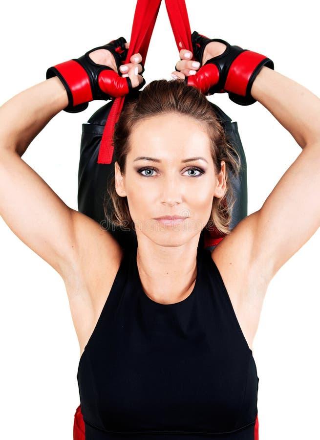 Entrenamiento activo joven de la mujer: el kickboxing cardiio, saco de arena fotos de archivo