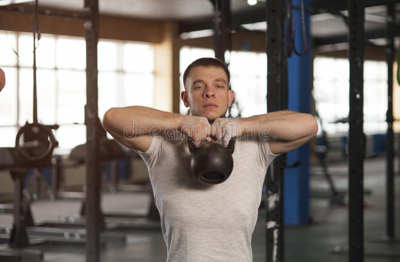 Entrenamiento apto y concentrado del hombre joven con Kettlebell en gimnasio imagenes de archivo