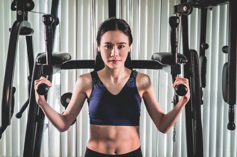 Entrenamiento asiático fuerte de la mujer en la máquina del gimnasio de la aptitud fotos de archivo libres de regalías