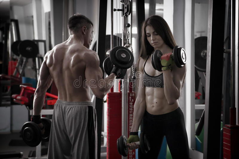 Entrenamiento atlético atractivo joven del hombre y de la mujer con pesas de gimnasia en gimnasio fotografía de archivo libre de regalías