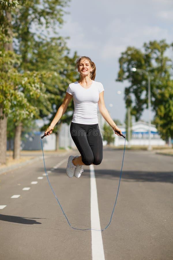Entrenamiento atlético de la mujer joven con una cuerda de salto en un fondo del parque Concepto del equipo de la gimnasia fotos de archivo