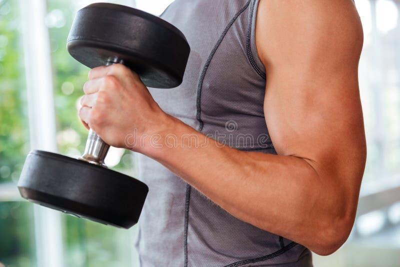 Entrenamiento atlético del atleta del hombre joven usando pesas de gimnasia en gimnasio fotos de archivo