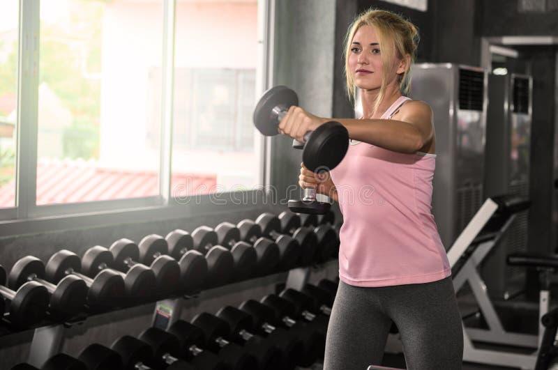 Entrenamiento atractivo de la mujer con pesas de gimnasia imagen de archivo