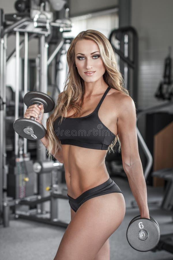 Entrenamiento atractivo rubio del culturista con pesas de gimnasia foto de archivo libre de regalías