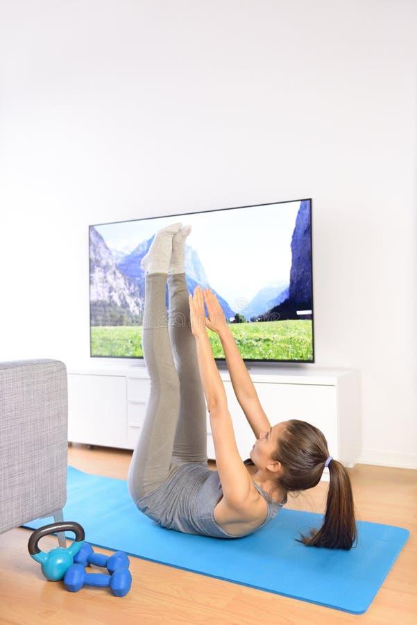Entrenamiento casero del ab de la aptitud delante de la televisión imagen de archivo