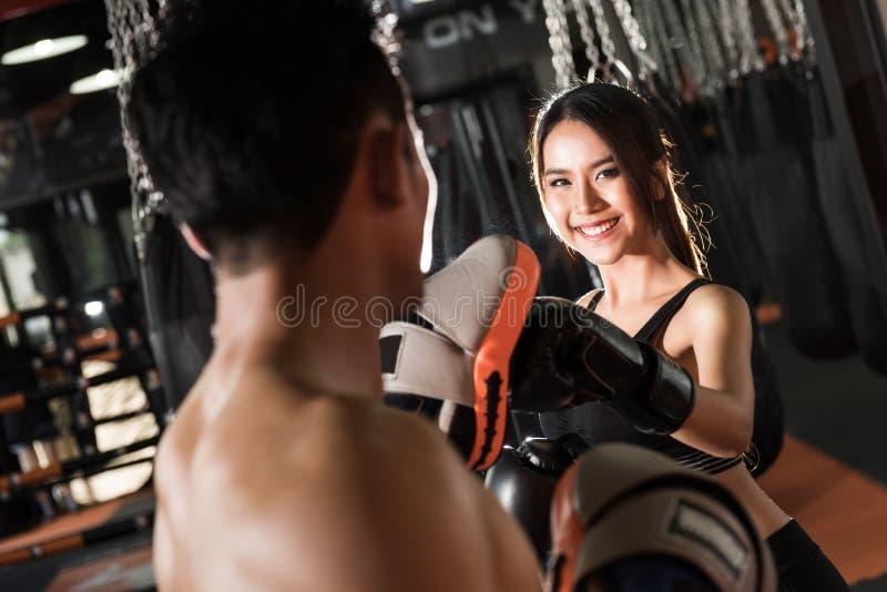Entrenamiento con los guantes de boxeo en el gimnasio, ejercicio de la mujer de los pares imagen de archivo