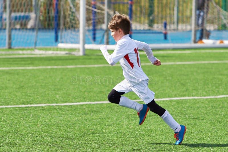 Entrenamiento corriente del jugador de fútbol del muchacho en campo de fútbol fotos de archivo libres de regalías
