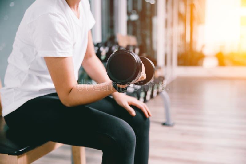 Entrenamiento de elevación del peso de la pesa de gimnasia de la mujer sana delgada del primer en club de deporte foto de archivo