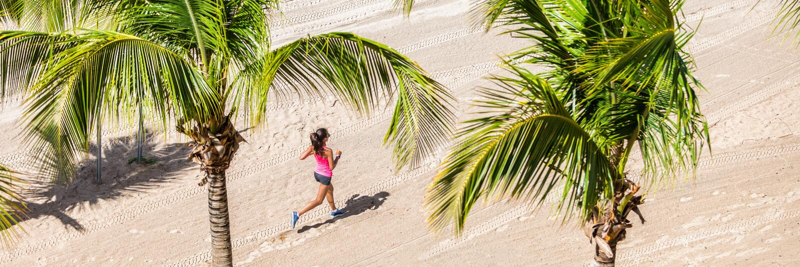 Entrenamiento de funcionamiento de la mujer de la aptitud en la playa tropical imagenes de archivo
