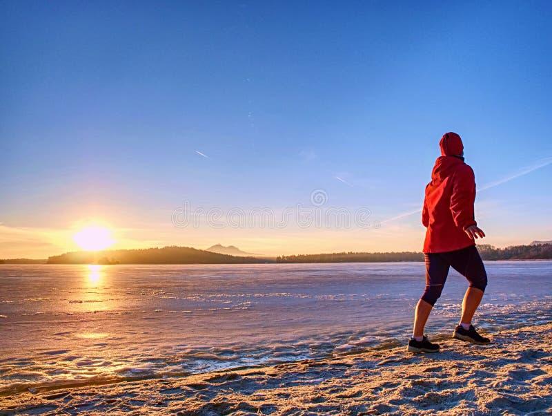 Entrenamiento de invierno regular Corre por un río congelado en una playa de arena imagen de archivo libre de regalías